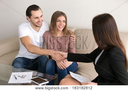 Cheerful happy young couple purchasing apartment. Guy shaking hands with real estate agent, male property buyer and female realtor handshaking, investment advisor congratulating clients with deal