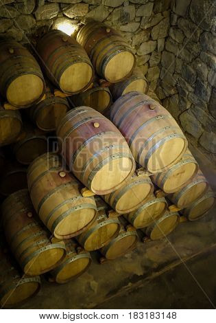 rows of wood wine barrels in a vintage winery cave