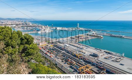Bright sunny day on the industrial shipping & transport hub & railyard in Barcelona.  Modern cityscape & coastline of Spain.