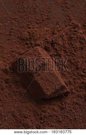 Close up of a chocolate bar piece covered with dark powder on a table