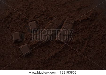Close up of a dark chocolate bar pieces covered in chocolate powder on a table