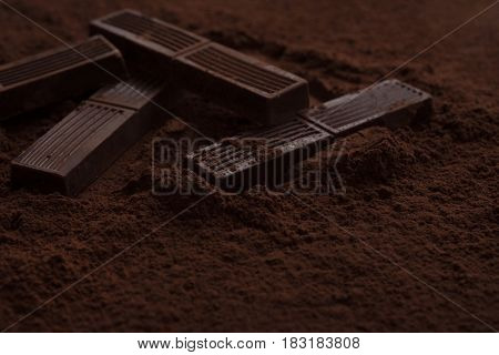 Close-up of chocolate bar pieces laying in chocolate powder on a surface