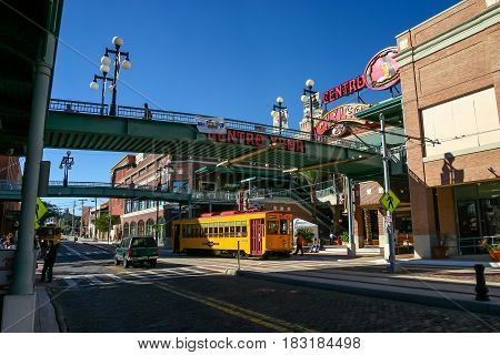 TAMPA, FLORIDA, US - November 29 2003: Footbridges to Centro Ybor entrance with yellow tram underneath and visiting tourists Tampa FL