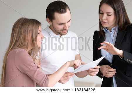 Male client holding documents and attentively studying them, discussing offer with female manager and wife, terms and condition of contract agreement, considering bank loan, health personal insurance