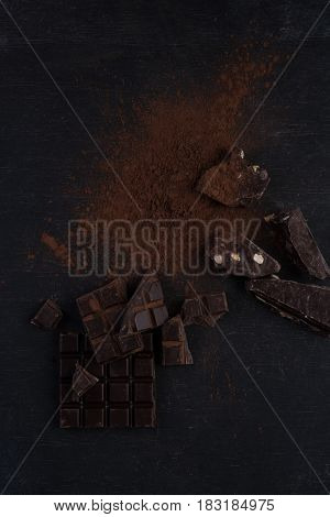 Top view of a dark chocolate bar crashed into pieces with chocolate powder over wooden background