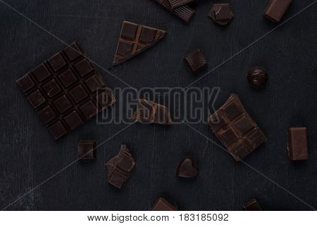 Top view of crushed dark chocolate bar with sweets over wooden background