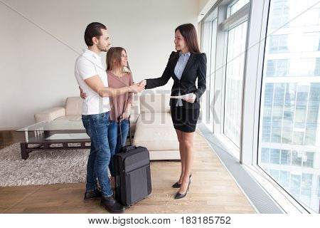 Cheerful couple from another city country searching apartment for rent, shaking hands with female broker, travelers with travel bag suitcase looking for short-term accommodation, moving in new home