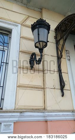 Architectural elements metallic black street lamp hanging on old house