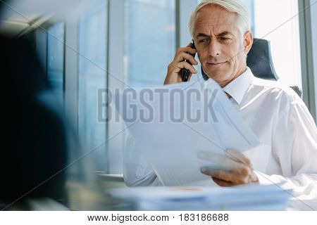 Shot of senior businessman sitting at his desk reading a document and talking on phone. Mature business professional working at his office desk.