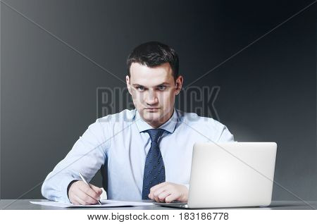 business man is sitting and working documents at his table with laptop