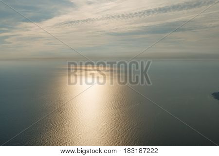 Blue sky with clouds and airplane trails over the Black sea. Sun train on the sea surface and a boat with boat trails on the water. Nature composition. in Crimea, Ukraine 2011.