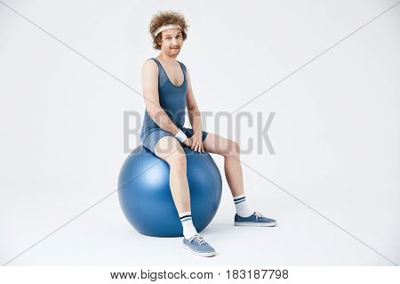 Man in blue sport clothing sitting on purple exercise ball, making faces and looking straight