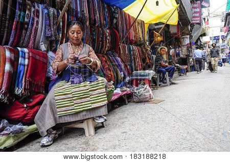 Dharamsala India september 8 2010: Old indian woman knitting in front of her shop on a local street market Dharamsala India.