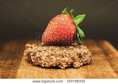 Brown oatmeal cookies with red strawberry on a wooden chopping Board