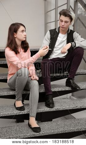 Teenage couple sitting on stairs and smoking