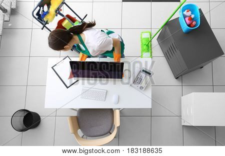 Young female cleaner at work in office