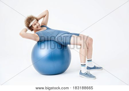 Tired retro man curling up on exercise ball. Looking exhausted, isolated on white background