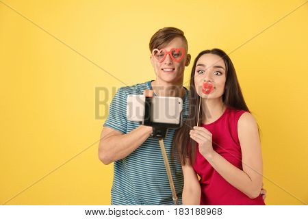 Happy young couple taking selfie on color background