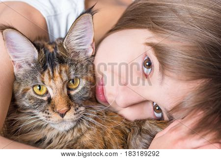 Happy little girl hugging lovely kitten. Cute ten year old child playing with her cat - close up. Portrait of beautiful kid holding on hands big fluffy Maine Coon kitty.