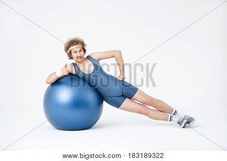 Man working on obliques, lying on his side, training with big purple exercise ball