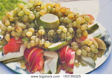 Wedding reception, restaurant catering, fruit platter. Fresh juicy fruits on big platter on table, close-up, nobody, objects
