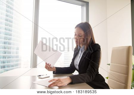 Attractive young woman wearing formal suit sitting alone at the office desk, holding some papers, reading agreements or contracts, female boss studying resume of job applicant at workplace