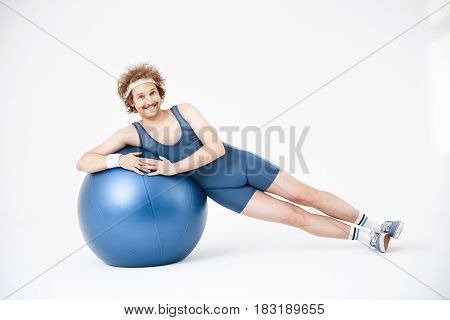 Nice smiling guy in sport wear lying over exercise ball. Side lying. Hands on ball