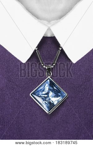 Blue crystal pendant over purple pullover with white collar closeup