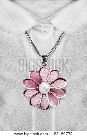 Pink flower pendant over white blouse closeup as a background
