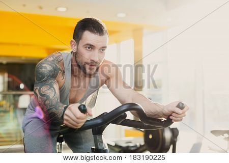 Young man with tattoo in fitness club. Cardio workout, ride stationery bike. Healthy lifestyle, guy training in gym. Flare effect