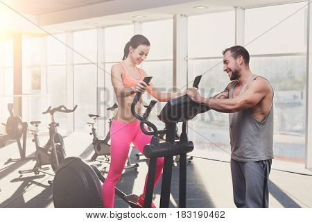Fitness instructor helps young woman on elliptical trainer. Cardio workout in gym, healthy lifestyle