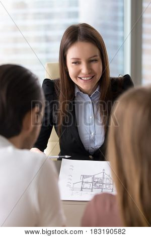 Vertical view of female cheerful project manager holding building project draft, smiling saleswoman showing architectural dream house plan to potential buyers, modern design or home improvement