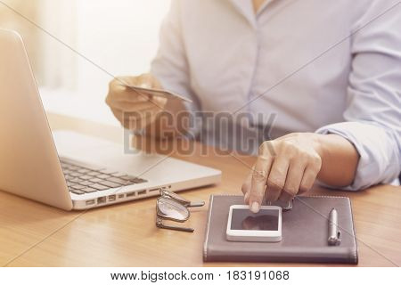 Business woman hands holding credit card and using mobile smart phone for online shopping.