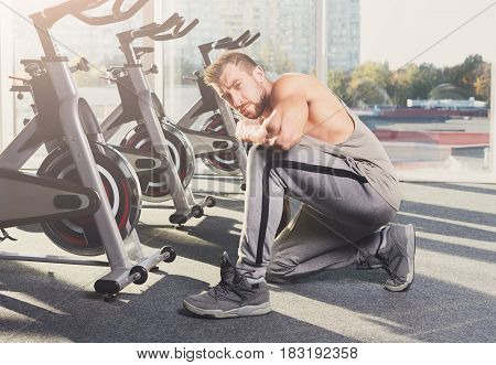 Little break. Handsome young man in sportswear relax after training in gym. Sexy guy with tattoo in fitness center