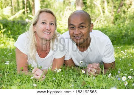 A Multiracial Mix Couple Lying On The Green Grass Park