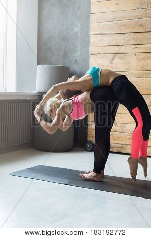 Yoga class instructor helps beginner to make back bend bridge exercise. Teacher assists young girl. Healthy lifestyle in fitness club. Stretching with coach