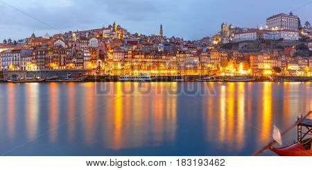 Panorama of Ribeira and Old town of Porto with mirror reflections in the Douro River during evening blue hour, Portugal, Portugal.