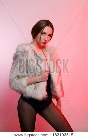 Fashionable Beautiful Woman In A Gray Fur Coat Of Artificial Fur On A Red Background Stands Frowning