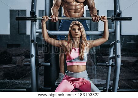 Fitness instructor exercising with his client at the gym. The beautiful blonde is engaged in sports. Handsome man, sports instructor