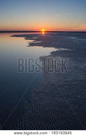 Sunset on a lake with a rugged coastline. Salt Lake Elton Russia.