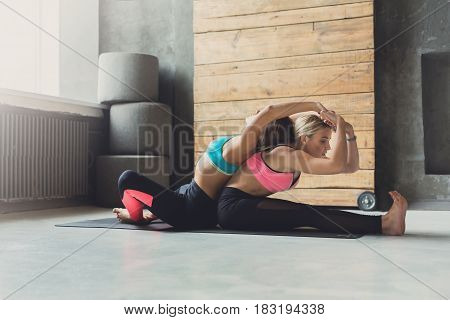 Yoga class instructor helps beginner to make back bend exercises. Teacher assists young girl. Healthy lifestyle in fitness club. Stretching with coach