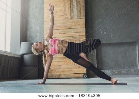 Woman in side plank pose at yoga class, Vasisthasana exercise. Fit yogi girl balancing on mat indoors at fitness studio gym