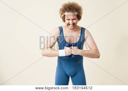 Retro man in old fashioned sport suit working hard on arm muscles with light dumbbells