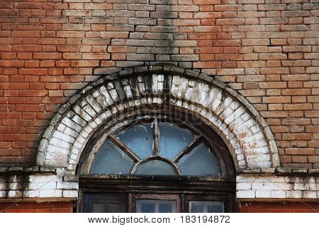 part of The old broken window Arch against a red brick wall
