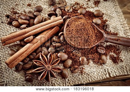 Coffee beans, ground coffee and cinnamon on burlap and wooden background.