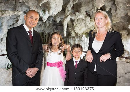 Family Dressed For A Celebration Made Up Of An Indian Man Accompanied By A Blonde Woman And Their Mi