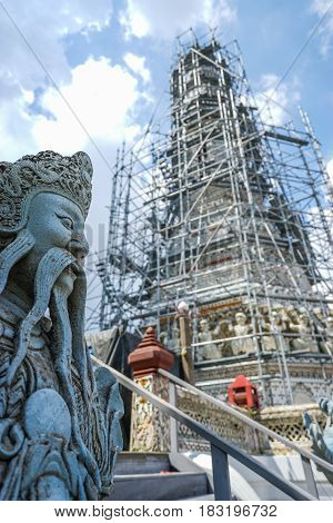 Chinese giant stone statue with renovated pagoda at Wat Arun temple Bangkok Thailand