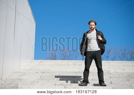 Thoughtful Young Man Sitting On Steps Against Blue Sky Background