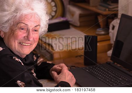 Happy grandmother sits at the table with a computer before learning to use the Internet
