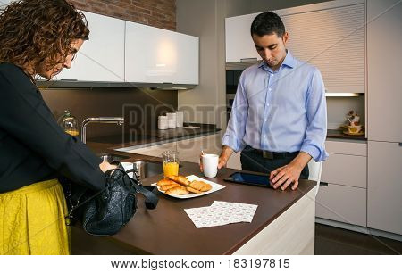 Curly woman preparing her bag while young man looking news in electronic tablet and having fast breakfast before go to work